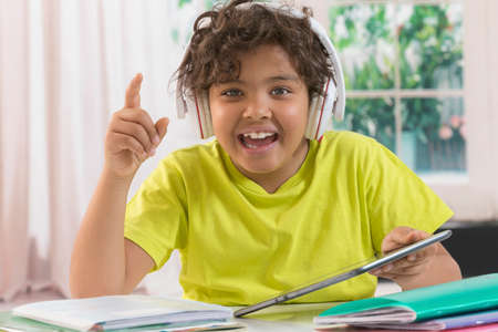 young boys: boy enjoying music on tablet music instead of working his lessons Stock Photo