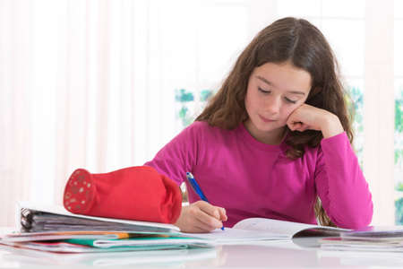 work at home: Little  girl concntrated on  homeworkat home