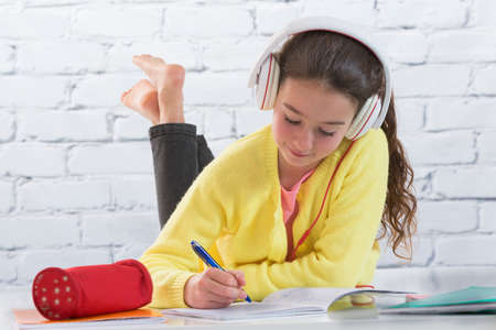 color pencil: Teen girl listening music  while making homework for school Stock Photo
