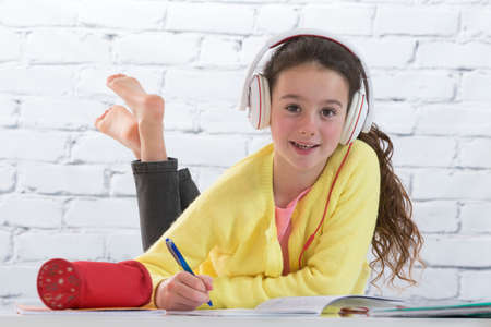 appreciating: Teen girl listening music  while making homework for school Stock Photo