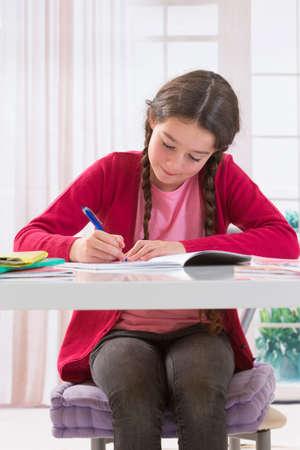 working on school project: Cute  little girl working on her school project at home Stock Photo