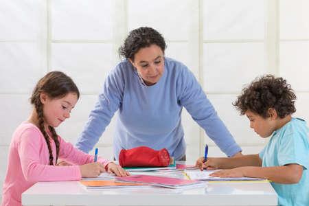 ni�os ayudando: Madre ayudar a los ni�os con la Tarea En la sala de estar