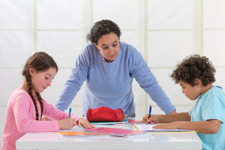 Mother Helping Children With Homework In living room