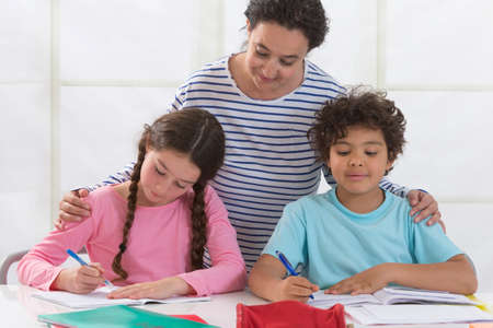 helping children: Mother Helping Children With Homework In living room