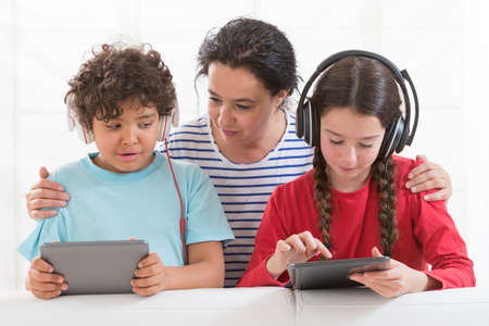 11 year old girl: Brother and sister playing with tablet pc under eyes of mother
