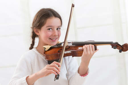 Cute child  playing violin and exercising at home Stock Photo