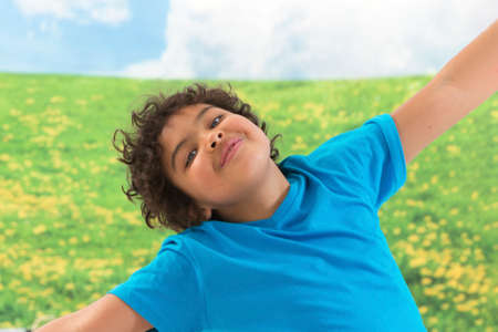 child laughing: little boy arms outstretched against green meadow