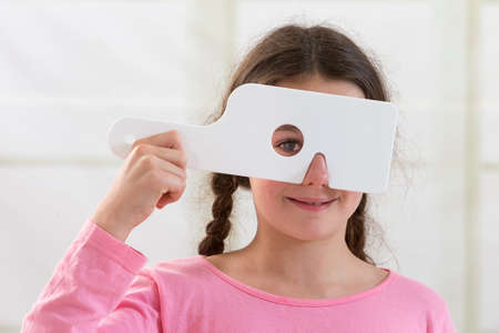 test equipment: Boy looking at vision test with one eye covered with occluder Stock Photo