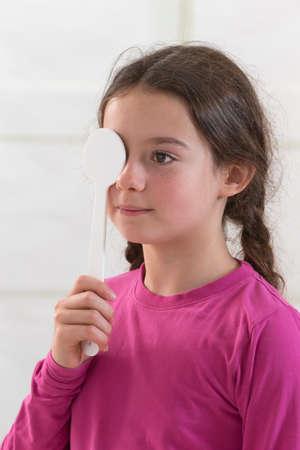 examen de la vista: Muchacho que mira el examen de la vista con un ojo cubierto con oclusor
