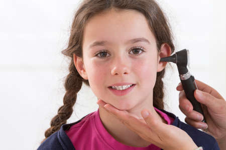 otoscope: Doctor Examining Childs Ears In Doctors Office Stock Photo