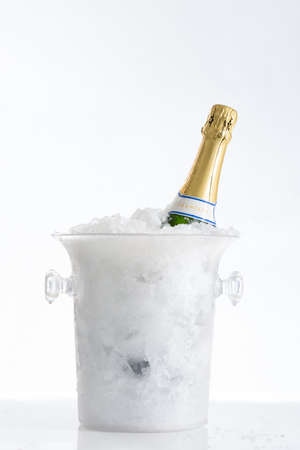 sektglas: Eine Flasche Champagner im Eimer isoliert auf weiß