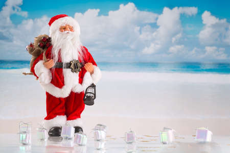 pere noel: Père Noël debout sur une plage avec de nombreux giffts sur le terrain Banque d'images