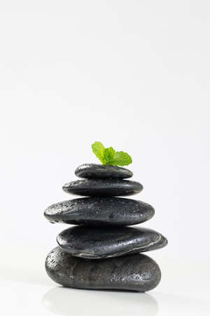 black stones: Mint leaves on  spa stones, isolated on white background.