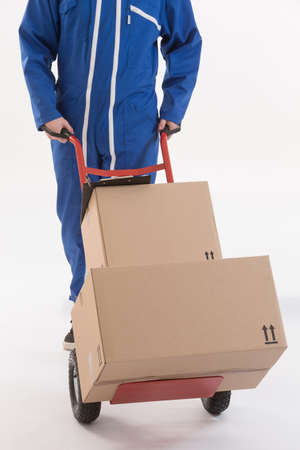 dolly: delivery man moving boxes with dolly, isolated on white background