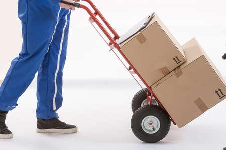 transporte: Homem de entrega de caixas com dolly em movimento, isolado no fundo branco