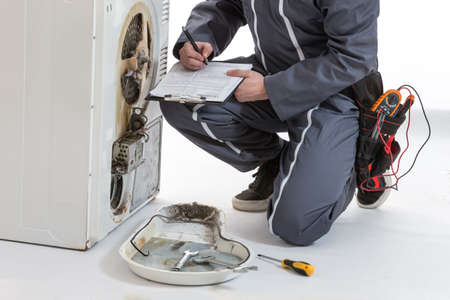 white wash: Male Technician repairing Washing Machine and Dryer