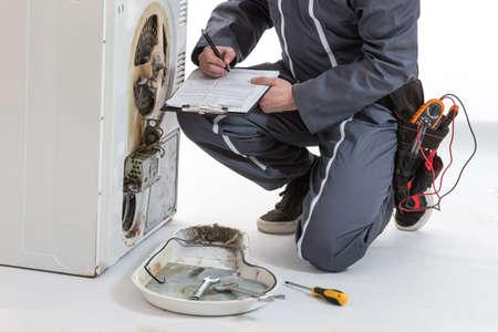 Man Technicus reparatie wasmachine en droger Stockfoto