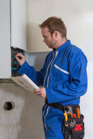 servicing: Technician servicing the gas boiler for hot water and heating