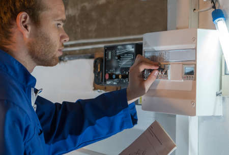 tallyman: Engineer adjusting thermostat for efficient automated heating system