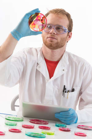 man doctor: Lab coat protected life science researcher observing potentially infectious cells in petri dish Stock Photo