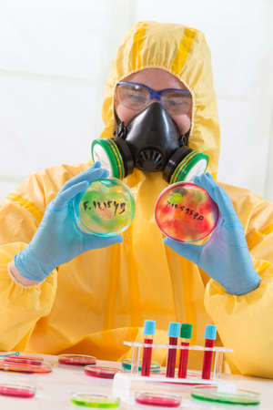 radiation protection suit: Scientist wearing protective suit and examining sample Stock Photo