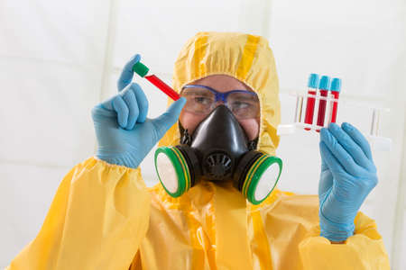 protective suit: Scientist wearing protective suit and examining sample Stock Photo