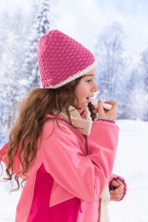 teen girl taking care od her lip with balm in winter Stock Photo