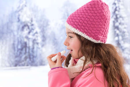 teen girl taking care od her lip with balm in winter Standard-Bild