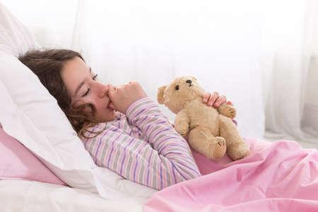 tumb: girl in Bed with Teddy Bear sucking her tumb Stock Photo