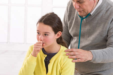 health professional: close up of hteen  girl and doctor hand with stethoscope listening to heartbeat Stock Photo