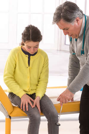 reflex: Doctor checking girl knee reflex Stock Photo