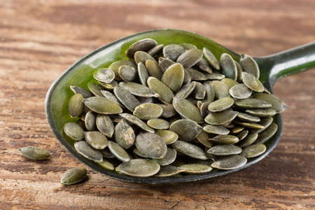pumpkin seeds i  spoon on wooden background