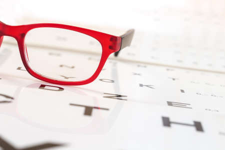 eye red: Reading red eyeglasses and eye chart Stock Photo