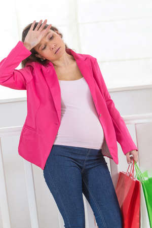 asian style: Young pregnant asian girl with the shopping bags on the white background Stock Photo