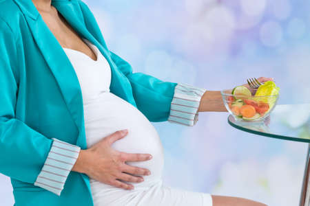 Beautiful pregnant woman with a bowl of salad, ready to eat Stockfoto