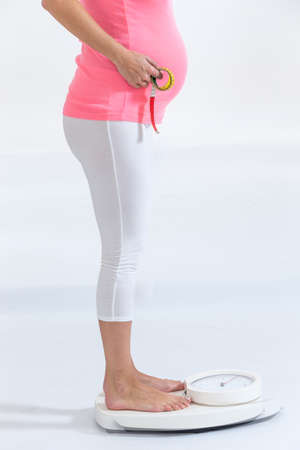 pregnant woman standing on weight scale Stockfoto
