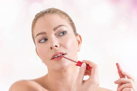 lipgloss: woman applying pink lipgloss to lips Stock Photo