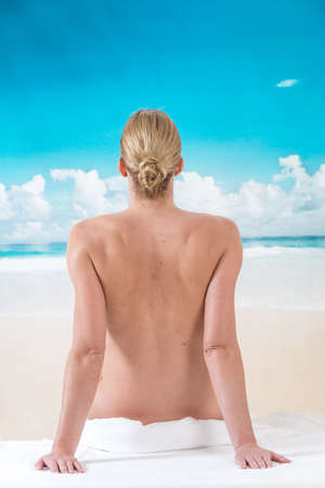 nude nature: beautiful woman sitting from the back on beach Stock Photo