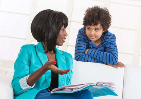 prime adult: Portrait of African mom helping son with homework.