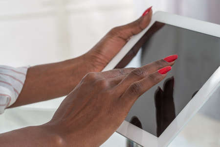 working hands: black female hands using digital tablet