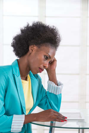 tormented: Portrait of mature black woman stressed at work