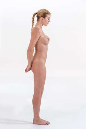 mujer rubia desnuda: mujer desnuda posa las manos sobre su espalda vista de perfil