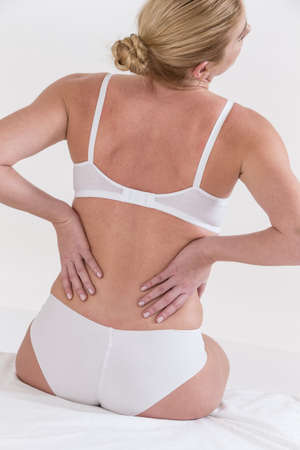 back ache: back ache for this woman sitting onher bed Stock Photo