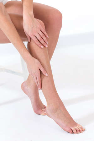 foot cream: Woman tacking care of her  legs sitting on white background
