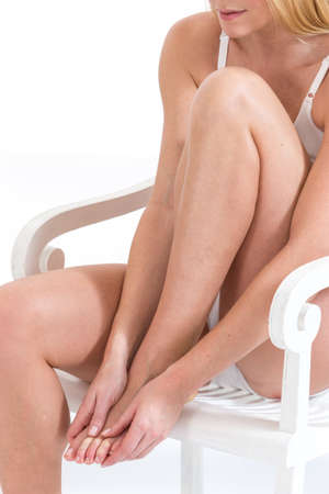 woman foot: Woman tacking care of her  legs sitting on white background