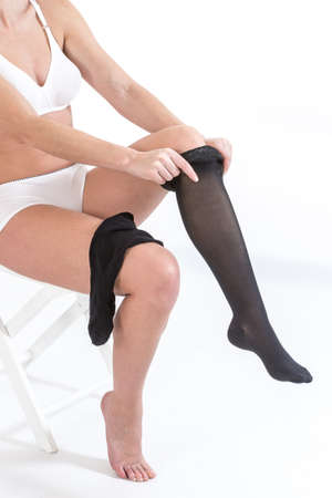 Woman putting anti-trombolic stockings on Stock Photo