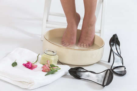 Femeninos que se relajan sus pies en un tazón de hidromasaje con agua Foto de archivo