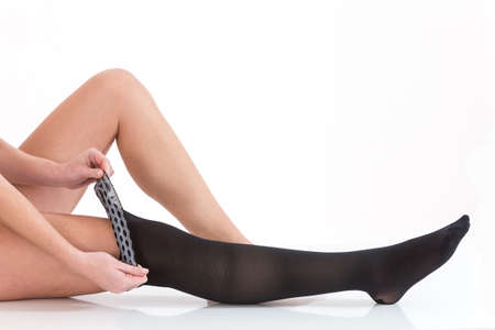 varicose veins: Woman putting anti-trombolic stockings on Stock Photo