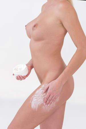 mujer desnuda: Mujer que aplica la crema hidratante cosmética Foto de archivo