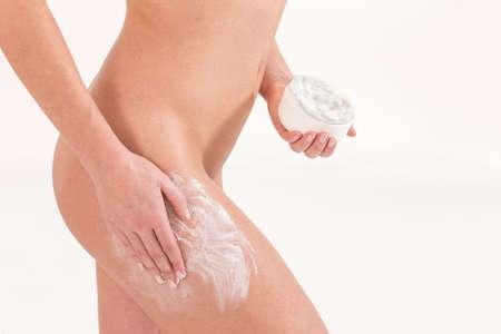 woman naked body: Woman applying cosmetic moisturizer cream